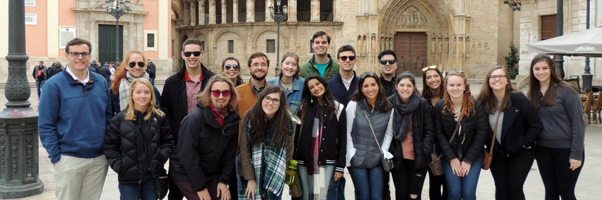 A large group of students stand at the Plaza Virgen in Valencia during the Spring 2018 study abroad trip